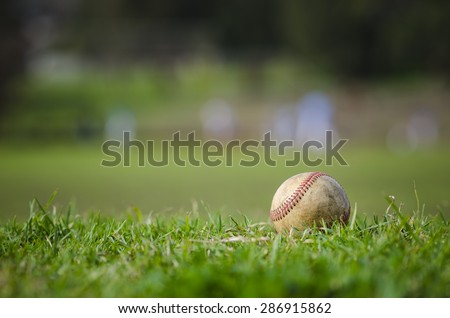 Used baseball laying on fresh green grass with baseball players in the background