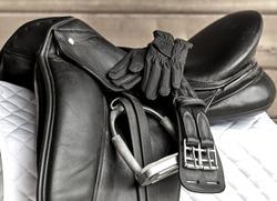 Used black dressage horse riding saddle with girth, stirrup and riding gloves on white saddle pad