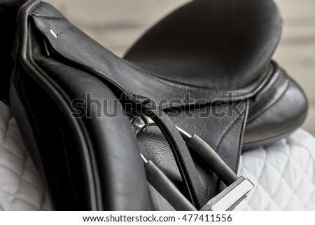 Used black dressage horse riding saddle with  white saddle pad and shallow depth of field