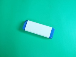 Used Blue Eraser with white cover Top View Isolated on Green Background.