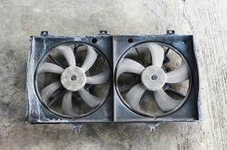 Used car radiator cooling fans on concrete background.