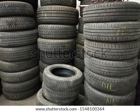 Used car tires, stacked on top of each other.  Seasonal  tire change.