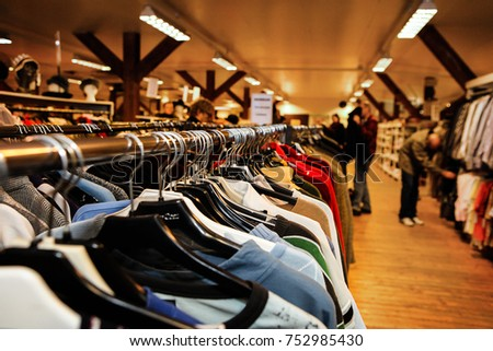 Used clothes on hangers in a thrift store. Out off focus, anonymous customers are seen in the background.