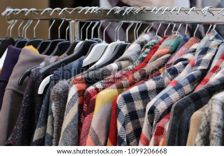 used clothes used in the coat hangers of a flea market outdoor #1099206668