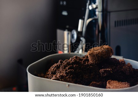 Used coffee grounds from espresso machine. Recycling compost container filled with used coffee waste. Coffee machine cleaning.