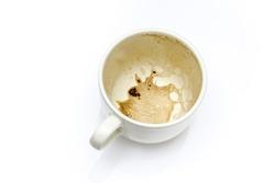 Used creamy coffee mug on white background