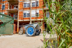 Used industrial obsolete wheelbarrow placed on building site, scaffold placed against edifice under construction for logistics need.
