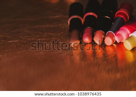 Used lipsticks. Nude lipsticks, lip balm. Close-up photo. Lipsticks laying down on golden surface. Colorful reflection. Lip care, beauty and fashion. Fashion and beauty blogger.   #1038976435