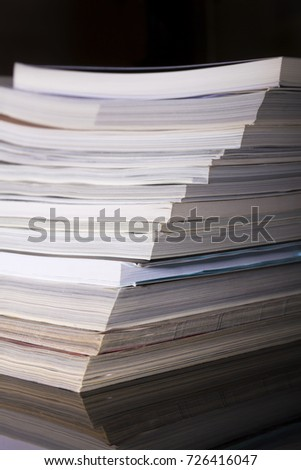 Used magazines - books stacked in a pile on a black background, a side view. #726416047
