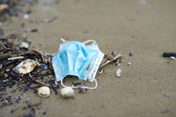 Used medical face mask left on the beach during the covid-19 pandemic. A used blue facemask left a shore. Prevention for flu and coronavirus.The spread of coronavirus on holidays through pollution.