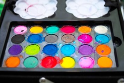 used multicolored watercolor of round shape on a black background,new watercolor paints twenty four colors,watercolors in a black plastic box