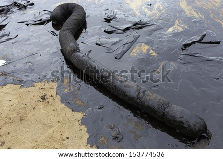 Used Oil Containment Boom on the sand beach that covered with Crude Oil on oil spill accident on Ao Prao Beach at Samet island on July 2013 in Rayong province, Thailand.