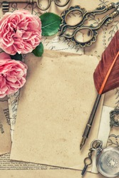 Used paper, antique feather pen, rose flowers. Vintage style toned picture