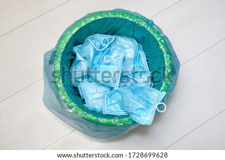 Used protective masks. Trowing facemask into the bin. Utilization of protection during. The end of pandemic. Quarantine time finishing. Hands in gloves and blue trash bag. Pollution of environment Foto stock ©