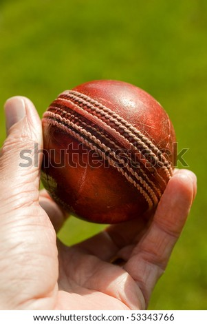 Used red leather cricket ball being held by hand against a green grass background
