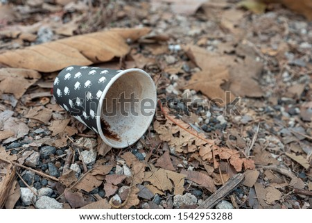 used single-use or disposable coffee cups thrown away on the flo #1542953288