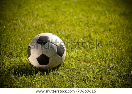 Used soccer ball on green grass