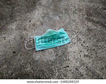 used surgical mask on the floor. discarded mask concept corona virus,covid-19. Stock photo ©