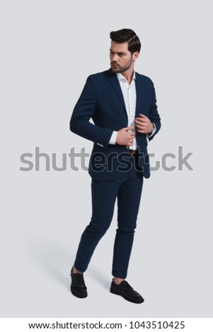 Used to look perfect. Full length of handsome young man in full suit looking away and adjusting his jacket while standing against grey background #1043510425