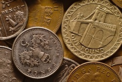 Used UK five pence coin on a pile of assorted GBP currency cash