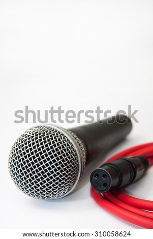Used vocal microphone with red xlr cable on the white background.