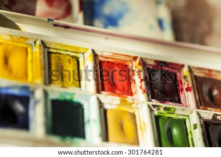 Used watercolour paint palette showing bright, well used paints