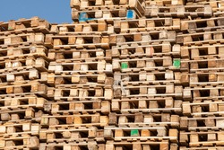 Used wooden pallets stacked on top of each other along a recycled lumber wall for loading and transporting goods. A bunch of platforms for industrial goods and boxes in the delivery service.