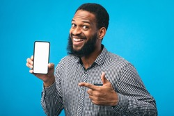 Useful App Or Website. Black man pointing at blank cell phone screen for advertising text, empty space, mock up