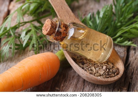 Useful carrot seed oil in glass bottle on the table close-up horizontal.