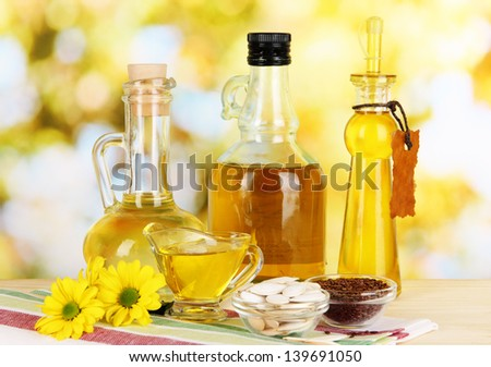 Useful linseed oil and pumpkin seed oil on wooden table on natural background