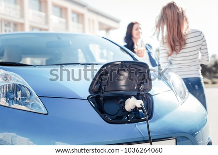 Useful nowadays. Blue comfortable electric car staying near girls and charging. #1036264060