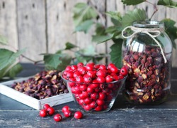 Useful properties of hawthorn berries. Harvesting of dried hawthorn for future use. Fresh red and dried hawthorn on a wooden background.Alternative traditional medicine using hawthorn.