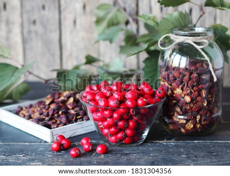 Useful properties of hawthorn berries. Harvesting of dried hawthorn for future use. Fresh red and dried hawthorn on a wooden background.Alternative traditional medicine using hawthorn. Foto stock ©
