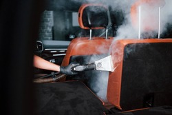 Uses steam cleaner. Modern black automobile is in service by woman inside of car wash station.