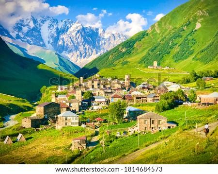 Ushguli village panorama in Enguri gorge with green Svaneti nature around in Caucasus mountains and horse riderin the foreground. Mestia.Georgia.