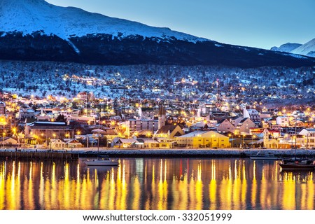 Shutterstock Ushuaia city in the late afternoon/night, lights on, lake in the foreground and snowed mountains in the background. Argentina, Patagonia, South America