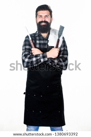 Using a barbecue set. Confident grill cook. Bearded man holding grill gripper tools. Hipster in apron with metal utensils for barbecue grill. Preparing food on grill.