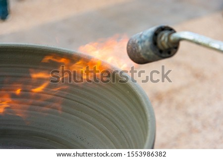 Using a flame launcher professional potter applies heat on clay spinning on the pottery wheel creating ceramic handcrafts at famous Thrapsano pottery village, Heraklion, Crete, Greece