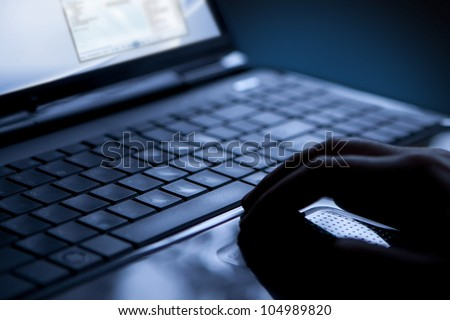 Using a laptop, finger on touchpad and keyboard
