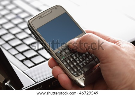 Using a PDA mobile phone with laptop keyboard background, blank screen for copy in high key