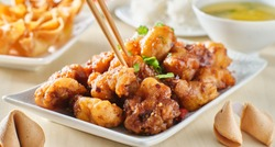 using chopsticks to eat chinese general tsos chicken meal with crab rangoon and egg drop soup