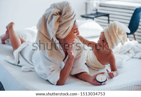 Using cream. Young mother with her daugher have beauty day indoors in white room. Foto d'archivio ©