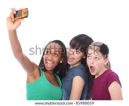 Using digital compact camera taking fun self portrait photograph for three pretty young teenager girl friends a blonde caucasian, an oriental Japanese and an African American mixed race student.