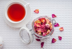 Using dry rose petals to make rose potpourri wich is great for home smell. Great way to preserving flowers and memories. Mason jar lid open filled with different color rose petals and tea cup with tea