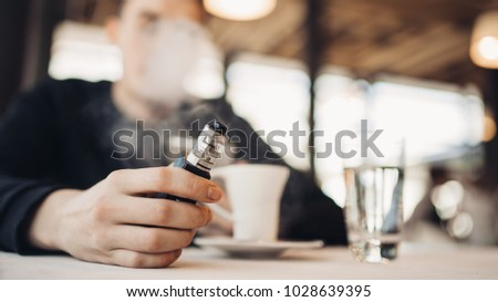 Using electronic cigarette to smoke in public places.Smoke restriction,smoking ban.Using vaping device with flavoured liquid.E-juice vaping new technology.Give up tobacco.Smoking habit,nicotine addict #1028639395
