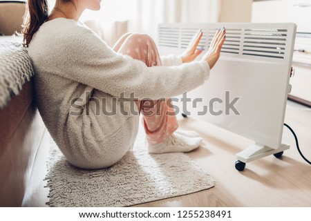 Using heater at home in winter. Woman warming her hands sitting by device and wearing warm clothes. Heating season. #1255238491