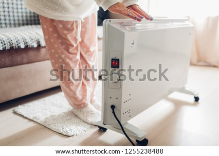 Using heater at home in winter. Woman warming her hands wearing warm clothes. Heating season. #1255238488