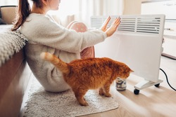 Using heater at home in winter. Woman warming her hands with cat. Heating season.