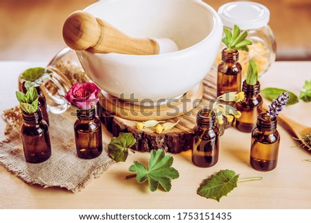 Using herbal essential oils in beauty products concept. Lot of various herbal oils with fresh plants on table above view. Vintage Instagram style filter. Foto stock ©