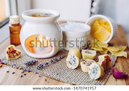 Photo of  Using homemade mini wax melts in aromatherapy lamp diffuser at home interior concept. Melts making ingredients on table for unbleached beeswax, solid coconut oil, essential oil, dried flowers.